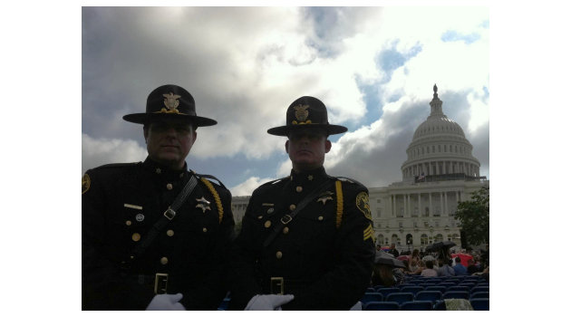 Two Honor Guard members standing in front of Capitol building and event
