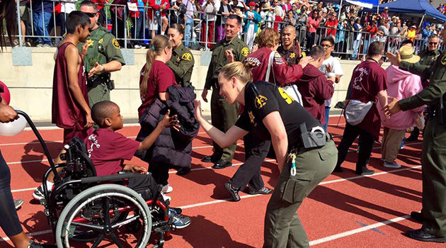 Child in wheelchair giving high-fives to Sheriff's Department officers