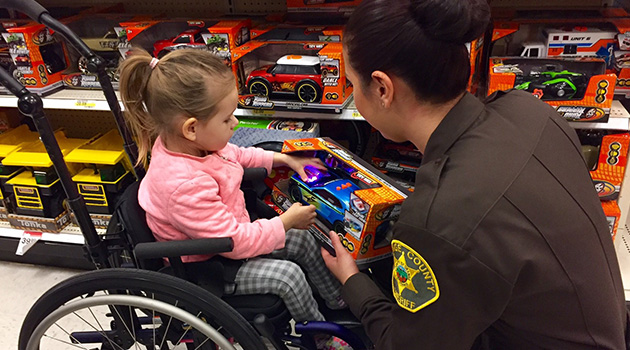 Child in wheelchair selecting a toy with a Sheriff's Department officer