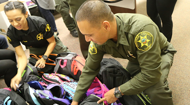 Two officers sorting through backpacks