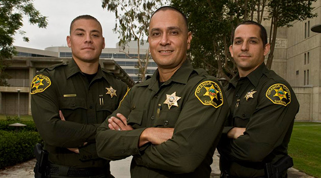 Three officers stand with arms crossed