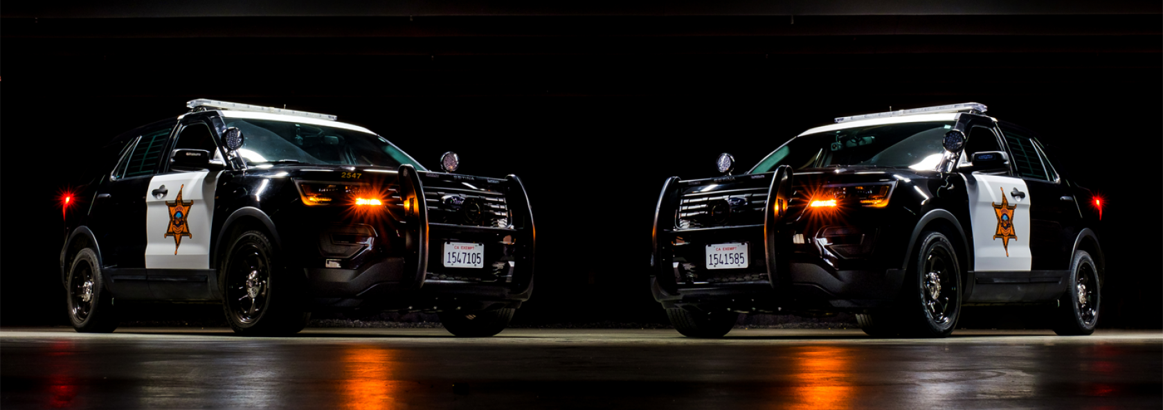 Two Sheriff patrol SUV's on black background